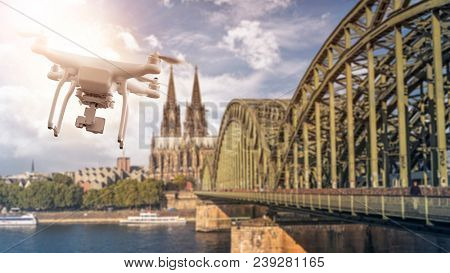multicopter drone flying next to the Hohenzollern Bridge across the rhine river, Cologne Cathedral in the back, Cologne, Germany