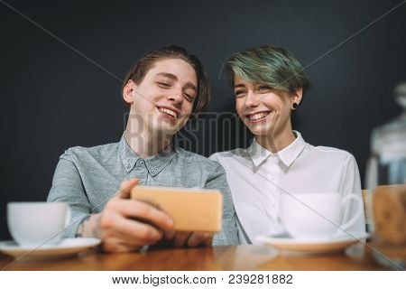 Friendship Bff Communication Concept. Best Friends Sitting At A Coffee Shop Laughing At Photos Or Fu