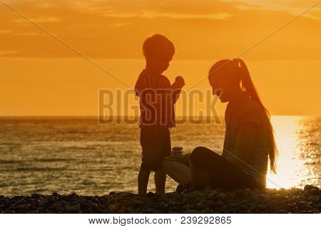 Mom And Son Playing On The Beach With Stones. Sunset Time, Silhouettes