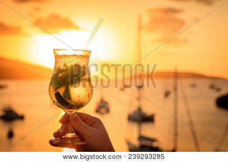 A glaass with mojito cocktail against sunset skies in British Virgin Islands