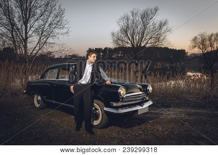Young Handsome Groom Is Next Near To Black Retro Car Sunset Background. Wedding With Vintage Old Ret