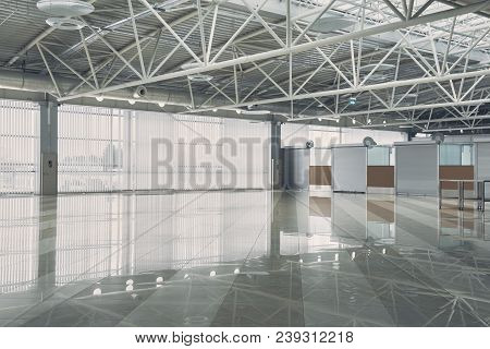 Wide Warehouse With Closed White Doors Leading In Accommodations. Ceiling Reflecting On Floor