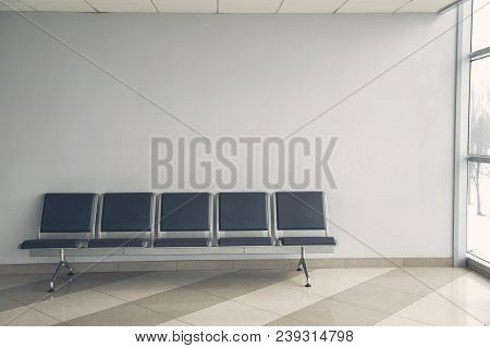 Waiting Room With Modern Cozy Chairs Locating Opposite Grey Wall. Copy Space