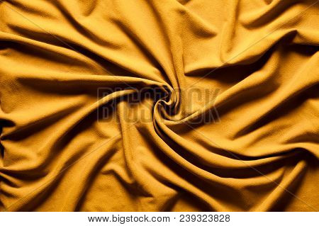 Drapery Fabric Gold Whirlpool. Wavy Background Vortex. A Fabric With Gold Colored Curves And Waves W