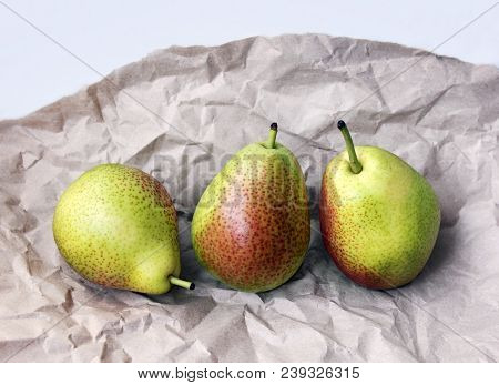 Still Life With Three Juicy Ripe Golden Pears On A Wrapping Paper. Selective Soft Focus And Space Fo