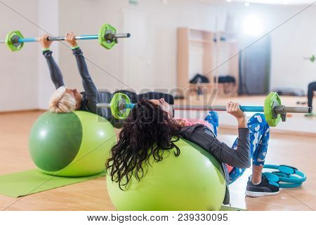 Back View Of Two Women Lifting Barbell Lying On Stability Ball While Exercising In Gym.