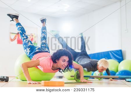 Two Women Exercising With Stability Balls Doing Push-ups In A Gym Class.