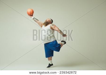 Excited Fat Man Is Throwing The Ball With Effort While Looking At It With Aspiration