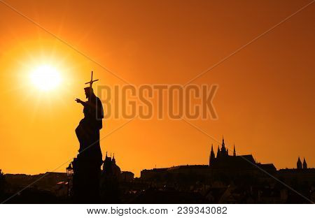 Sunset Backlit Silhouettes Of Statues And Roofs Of Cityscape Skyline At Charles Bridge In Prague, Cz