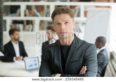 Serious Corporate Worker Looking At Camera, Company Associates Discussing Business Behind. Portrait