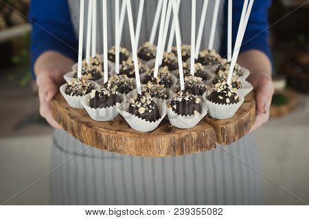 Platter of cake pops with chocolate icing in hands of waitress. Candy bar and catering concept for birthday, wedding and other holiday celebration poster