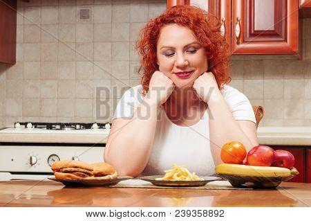 Big Woman Eat Fast Food. Red Hair Fat Girl With Burger, Potato And Fruit. Unhealthy Food Concept Wit