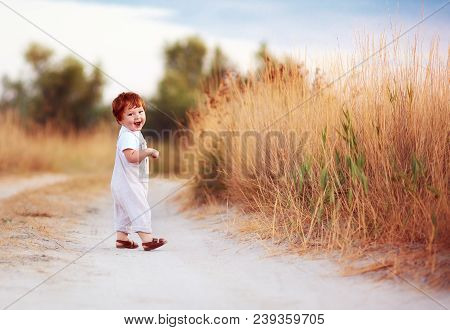 Cute Redhead Baby Toddler Walking Along The Summer Path