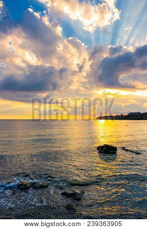 Gorgeous Sunrise At The Seaside. Sunbeams Come From Behind The Cloud. Sun Reflects On Rippled Water