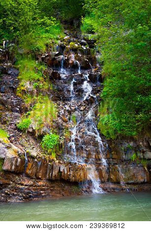 Small Waterfall In Forest. Lovely Summer Nature Scenery. Fresh And Clean Environment. Located In Syn