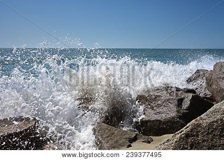 Waves Crash Against Rocky Ocean Coastline, With Blue Sky