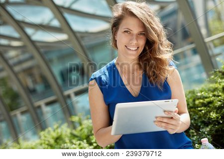 Young woman holding tablet, sitting outdoors, smiling happy.