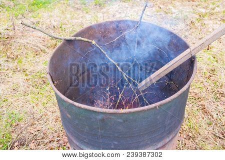 Burning Garbage In Old Iron Barrel. Cleaning Of The Countryside Area After Winter