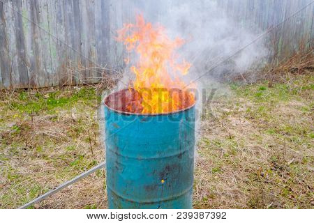 Burning Garbage In An Iron Barrel. Cleaning Of The Countryside Area After Winter
