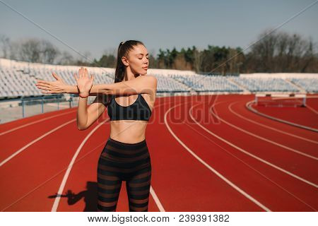 Sport Fitness Woman Stretching On The Stadium.sport Blond Girl Stretching Arms In Sport Running Aren