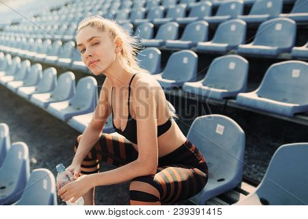 Sporty Young Attractive Girl In Sportswear Relaxing After Hard Workout Sit And Drink Water From Bott