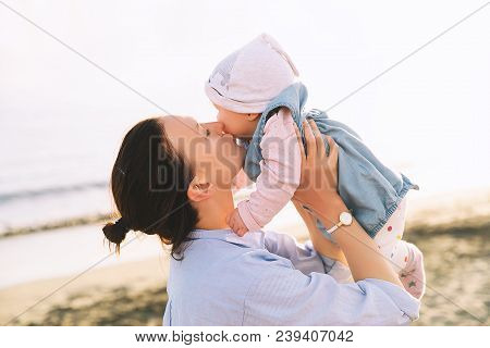 Mother And Baby At Sunset On The Beach Ocean In Summer. Woman And Her Child Playing Together Outdoor