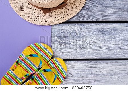 Flip-flops And Straw Hat. Flat Lay, Top View. Wooden Desk Surface Background.