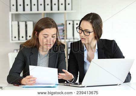 Two Executives Working Together Talking About Documents At Workplace
