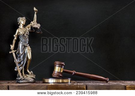 Statue Of Lady Justice With Judges Hammer On Black Board Background