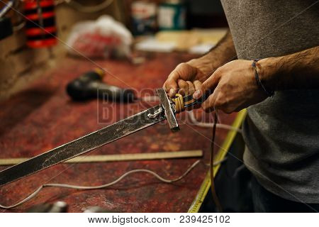 Smith Makes Leather Winding Of Sword. Man Is Working In Workshop. He Fixes Leather Band On Hilt Of S