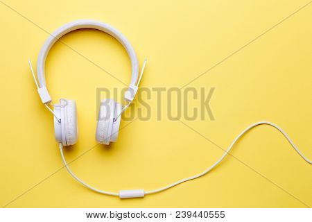 Image of white headphones for music on yellow background
