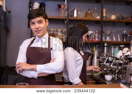Asian Male Barista Loking To Camera With Attractive Smile In Coffee Shop Counter.  Barista Male Work