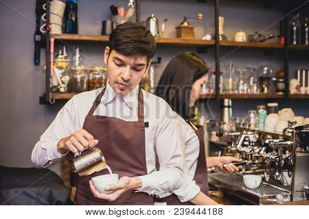 Asian Male Barista Making Coffee In Coffee Shop Counter.  Barista Male Working At Cafe. Man Working