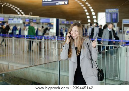 Pretty Girl Speaking By Smartphone At Airport Hall, Wearing Grey Coat And Bag. Concept Of Conversati
