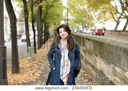 Asian Charming Female Tourist Walking On Autumn Street With Fallen Leaves In Europe. Concept Of Inte