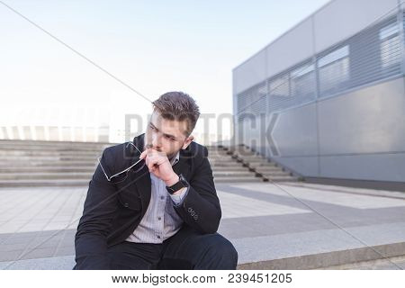 Frustrated Businessman Is Sitting On The Ladder At The Sad. A Depressed Man Is Sitting On The Street