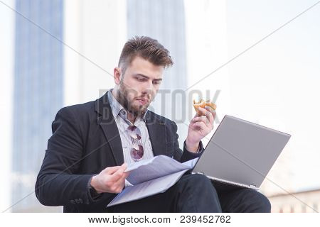 Portrait Of Busy Man With Laptop, Business Papers And Snack In Hand In The Open Air. A Busy Business