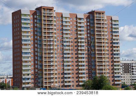 A Multi-storey Brick Building Under Construction, Against A Blue Sky Background. High Multi-story Bu
