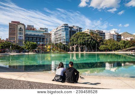 Santa Cruz De Tenerife, Canary Islands, Spain - Desember 11, 2016: Couple Sitting On The Boder Of Wa