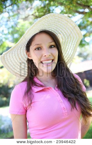A cute teenage girl smiling in the park with straw hat