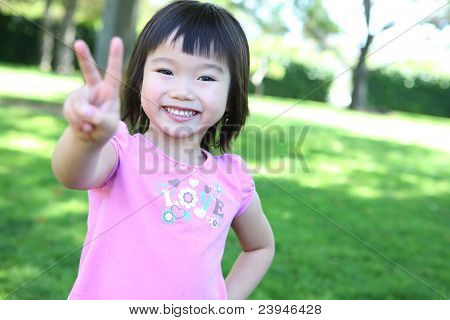 Cute young asian girl in the park having fun
