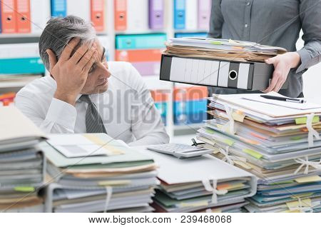Stressed Businessman Working At Office Desk And Overloaded With Work, The Desktop Is Covered With Pa