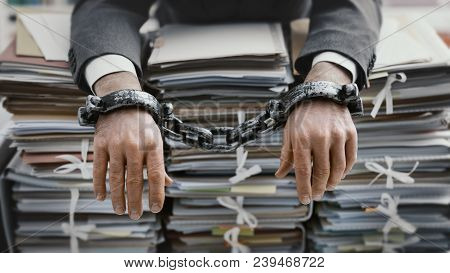 Overworked Stressed Businessman Chained To The Workplace, He Is Overloaded With Work And Lying On Pi