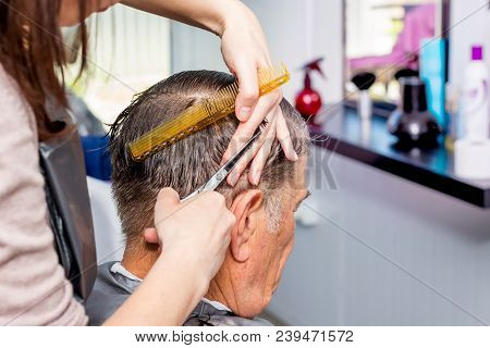 Master In Hairdressing Salon Makes  Stylish Hairstyle For An Elderly Man