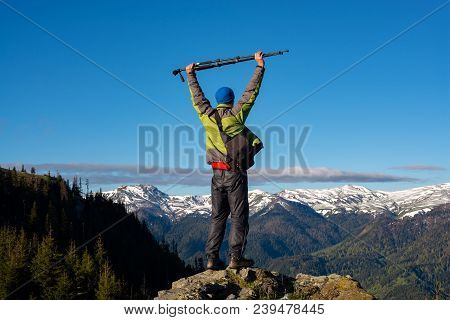 Adventurer, Photographer With Open Arms Is Standing On The Rock, Admiring The Stunning Mountain Rang
