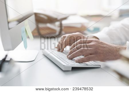 Businessman Working With His Computer In The Office, He Is Typing On The Keyboard, Hands Close Up