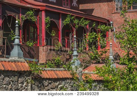Wild Grapes On The Walls Of A Buddhist Temple In Central Europe. Wooden Terrace Of Red Building With
