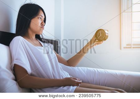 Young Asian Woman Hates Getting Stressed Waking Up Early,female Stretching Her Hand To Ringing Alarm