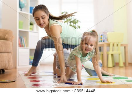 Young Mother Playing Twister With Her Kids. Cheerful Family At Home. Happy Family Having A Fun Toget