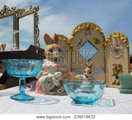 Stand With Vintage Porcelain Rabbits, Glass Dishes And More At Flea Market.